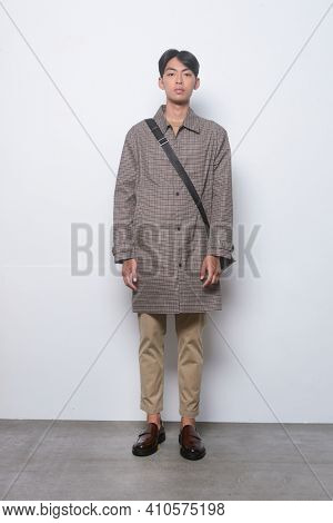 full length young handsome man wearing in coat with shirt and khaki pants , brown shoes with handbag posing in studio