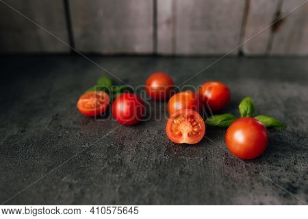 Red Cherry Tomatoes With Green Basil On A Gray Background