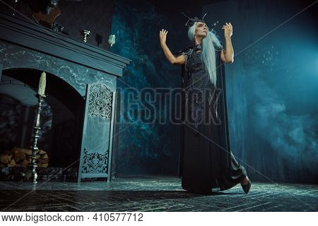 Beautiful old woman with long gray hair in a rich headdress and  black dress poses in the rays of light in a dark castle. Black Queen, Witch. Halloween.