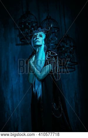A portrait of a stately and beautiful old woman with long gray hair, in a rich headdress and black dress against a dark background. Black Queen, Witch. Halloween.