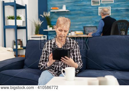 Middle Aged Lady Relaxing On Sofa Reading On Tablet Pc Anjoying Content. Elderly Woman Using Moder T