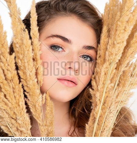 Teen girl with a clean skin of face, isolated.   Beautiful young  woman with healthy skin face. Skin care concept. Closeup female face with a freckled. Young woman holds a bunch of wheat.