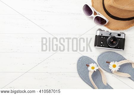 Summer vacation items and accessories. Flip flops, sunglasses, camera and sun hat on wooden table. Top view flat lay with copy space