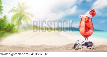 Fresh cold cocktail on tropical beach with palms and bright sand. Summer sea vacation and travel concept