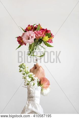 Wine Glass Full Of Fresh Pink, Red And White Spring Flowers In Hand Of Woman In White Blouse, White