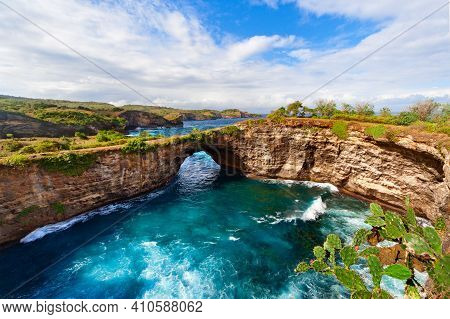 Natural Stone Bridge Over Sea Pool In Broken Bay Beach In Nusa Penida Island. Popular Bali Travel De