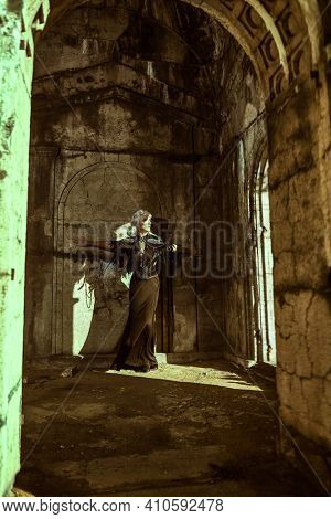 Aristocratic sad old widow woman in a rich black dress stands in ruined castle and looking to the window. Black Widow. Fantasy World.