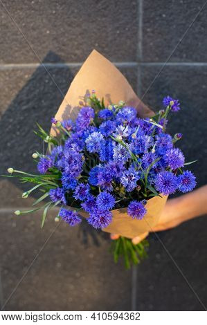 Hand With A Bouquet Of Blue Cornflower In Craft Paper. Grey Wall On Background. Blue Seasonal Flower