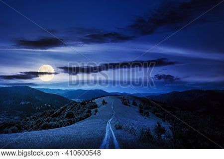 Road Through Meadow In Mountains At Night. Beautiful Rural Landscape Of Carpathians In Full Moon Lig
