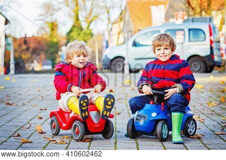 Two Little Kids Boys In Colorful Clothes And Rain Boots Driving Toy Cars. Twins Making Competition,