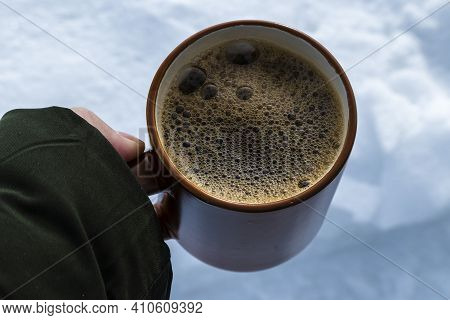 A Large Brown Cup With Strong Coffee In The Hand Of A Man Against The Background Of Snow. An Invigor