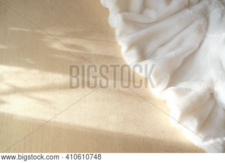 White Delicate Soft Background Of Plush Fabric Folds On Light Golden Background With Shadow And Sunl