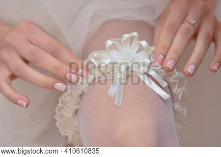 Slender Sexy Bride Puts A Garter On Her Leg Close-up.