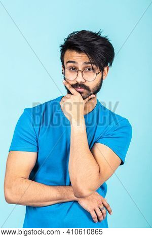 Emotional Portrait Of A Handsome Hindu Man In A Blue T-shirt On A Bright Blue Background, Think Abou