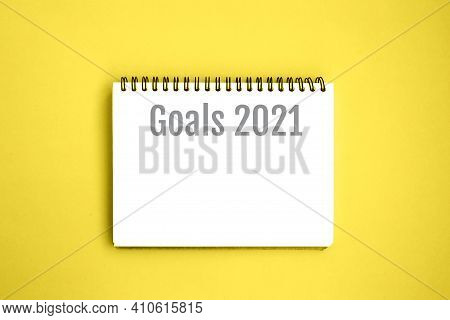 Open Notebook With White Blank Pages On Yellow Background. Notepad With An Inscription: Goals 2021.