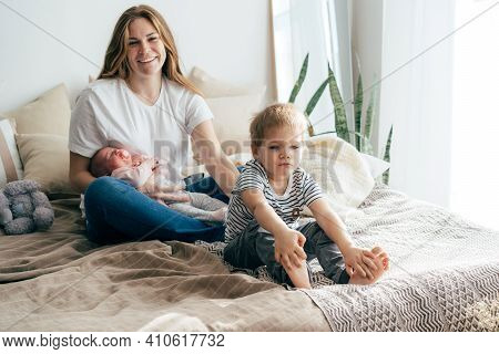 Mom With Children On The Bed. The Baby Is In Moms Arms, The Toddler Sits Next To Him, Offended. Two