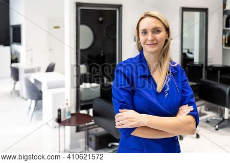 Young Attractive Confident Professional Beautician Doctor Portrait In Blue Uniform At Beauty Clinic