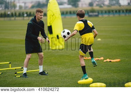 Young Man Coaching Soccer Boy. Coach On Training Session With Teenage Boy. Soccer Player Kicking Bal