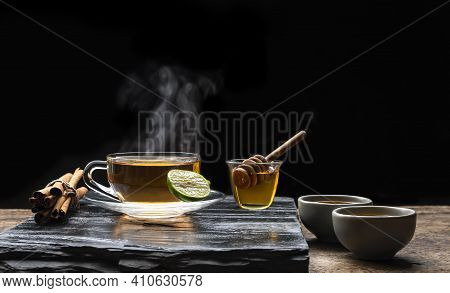 Aromatic Herbal Hot Tea In Glass Teacup With Steam And Honey On Black Stone Plate In Dark Background