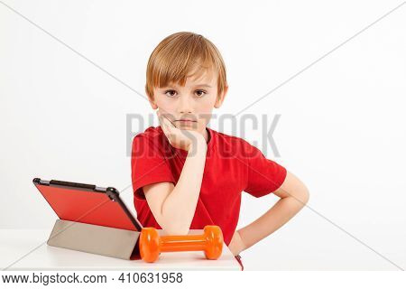 Cute Boy With Tablet Doing Sport Exercises At Home. Online Education, Sport During Pandemic. Sporty