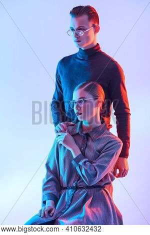 Handsome young man and beautiful young woman posing together in stylish glasses. Optics style. Fashion studio shot.