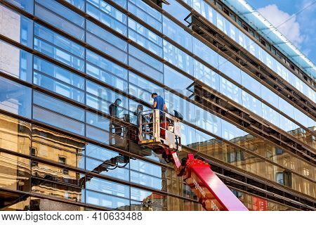 Munich, Germany - September 12, 2018: Workers In Construction Cradle Washing Windows Of A Skyscraper