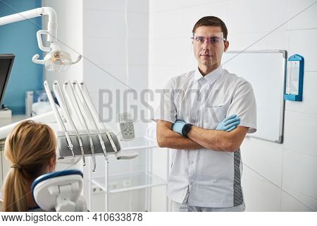 Dental Surgeon Standing With Crossed Arms In His Office