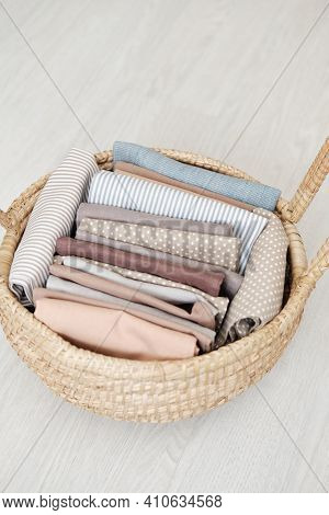 Neatly Folded Natural Cotton Fabric In A Wicker Straw Basket With Handles On A Gray Wooden Backgroun