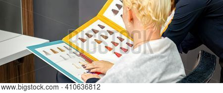 Professional Female Hairdresser And Female Client Choosing Hair Dye Color From Hair Color Samples In
