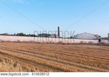Freshly Picked Dry Cereal Field With Factory In The Background, In Southern Andalusia Spain.