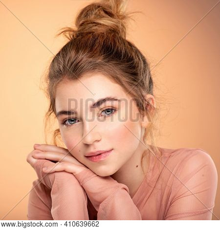 Closeup portrait of an young  girl over colored background.  Photo of a fashion model posing at studio. Pretty young woman with  brown hair looking at camera. Beauty portrait.