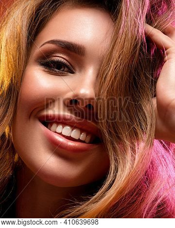 Portrait of happy beautiful young woman with bright shiny makeup. Smiling Blonde with brightly colored long hair. Pretty girl with long curly hair.   Fashion model touching her hair.