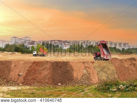 Dump Truck Dumps Soil At A Construction Site. Backfilling Of The Foundation With Ground For Objects,