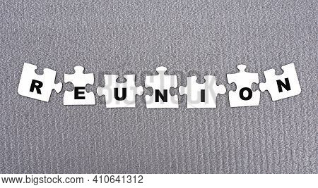 Reunion - Word Composed Of Paper White Puzzles On A Gray Background. Info Concept