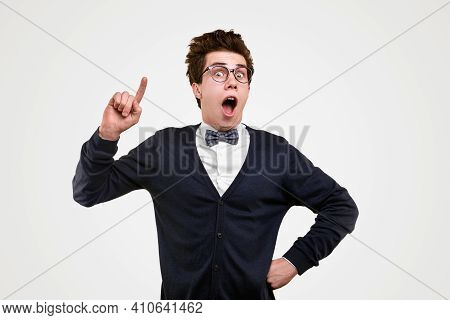 Funny Young Male Genius In Nerdy Suit And Glasses Pointing Up And Looking At Camera With Excited Fac