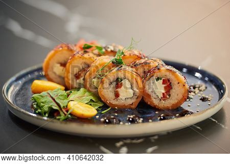 A Close-up Photo Of Sushi Rolls With Salmon, Philadelphia Cheese, And Tuna On A Blue Ceramic Plate W