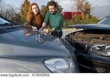 Car Crash And Man And Woman Reporting Damages