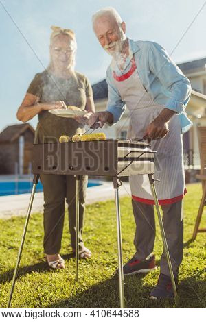 Senior Couple Having A Backyard Barbecue Party, Grilling Meat And Corn, And Having Fun Spending Leis