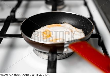 Fried Eggs In Frying Pan, Close-up. Small Frying Pan Standing On Gas Stove, Indoors. Selective Focus