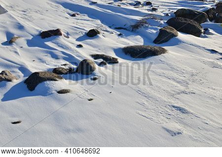 Stones On The Ground And Grass Covered With Snow In A Blizzard During The Onset Of The Winter Season