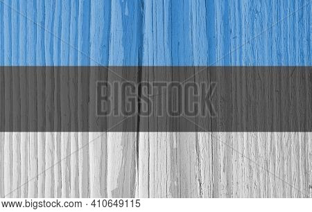 The Flag Of Estonia On Dry Wooden Surface, Cracked With Age. Light Pale Faded Paint. Background, Wal