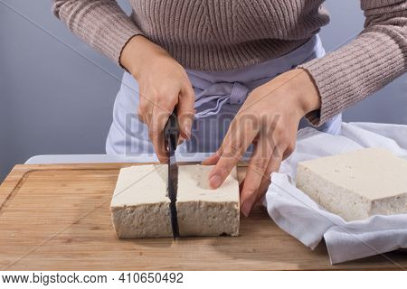 Tofu On Hand, White Tofu On Wooden Cutting Board.