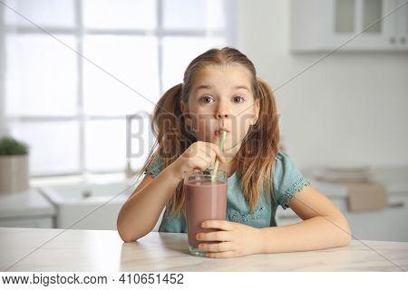 Cute Little Child Drinking Tasty Chocolate Milk In Kitchen