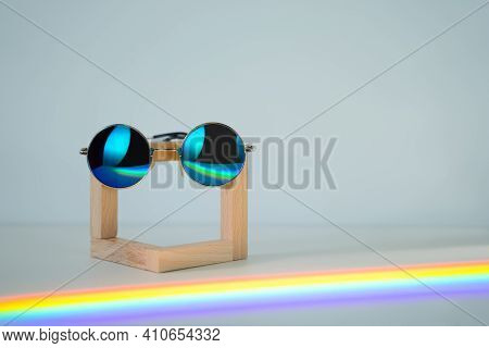 Blue Reflective Sunglasses On Wooden Stand In Front Of A White Background With Raibow Reflections In