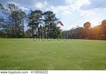 Background Of Evening Golf Course Has Sunlight Shining Down At Golf Course. Nice Scenery On A Golf C