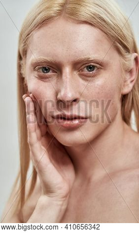 Portrait Of Handsome Young Caucasian Man With Long Fair Hair Tightening His Cheek And Looking At Cam
