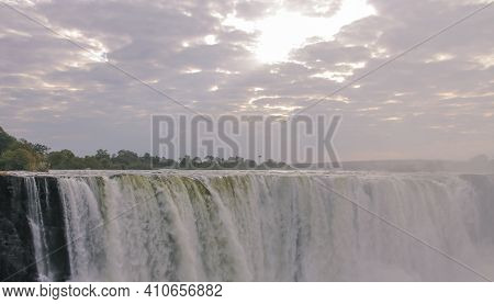 View Of A Cloudy Landscape With Morning Sun Rays Over Victoria Falls. The Rising Sun Breaking Throug