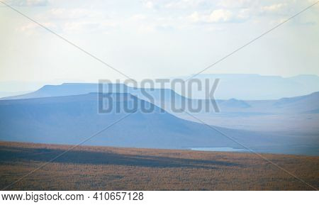 View Of The Distant Typical Mountains Of The Putorana Plateau From A Helicopter. Autumn Landscape Of