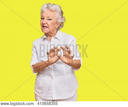 Senior grey-haired woman wearing casual clothes disgusted expression, displeased and fearful doing disgust face because aversion reaction. with hands raised