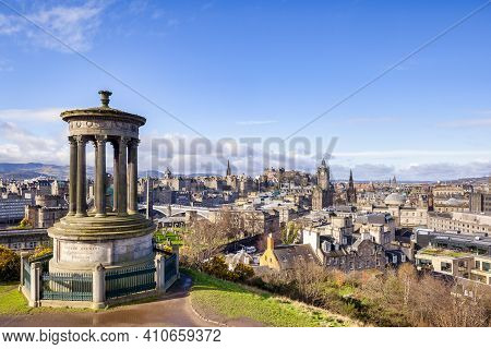 A View Of Central Edinburgh From Calton Hill, With The Dugald Stewart Memorial In The Foreground.